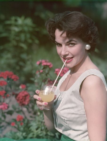 Short-haired brunette, wearing a striped, sleeveless summer top & pearlised button earrings, sips orange juice from a Britvic glass through a very long straw
