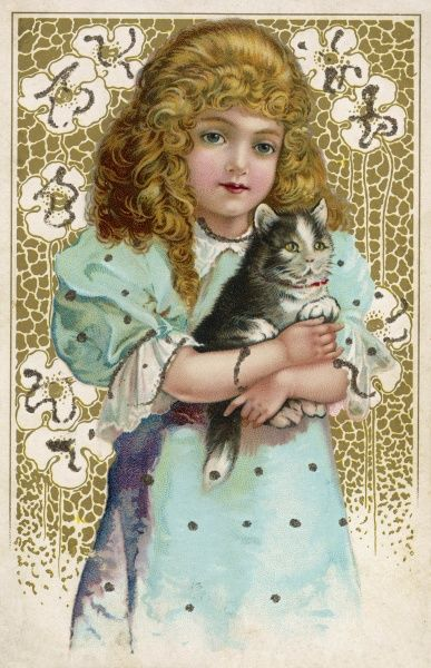 A little girl with blonde ringlets holds her cat in her arms and smiles sweetly