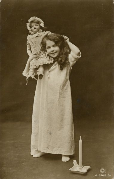 A girl in her nightdress about to take her doll to bed  1915