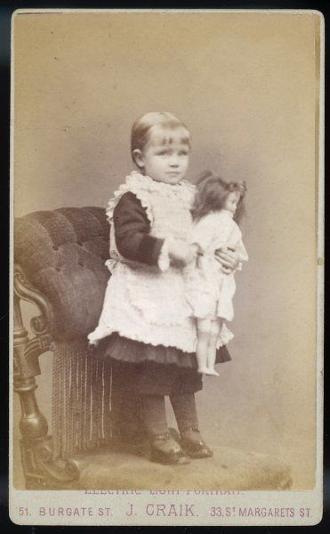 A little girl with her doll stands on an ornate velvet chair to have a photograph taken at an Electric & Daylight studio