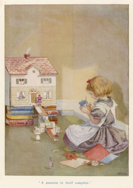 A young girl sits on the floor with her doll's house and cuts from paper some human figures to inhabit it