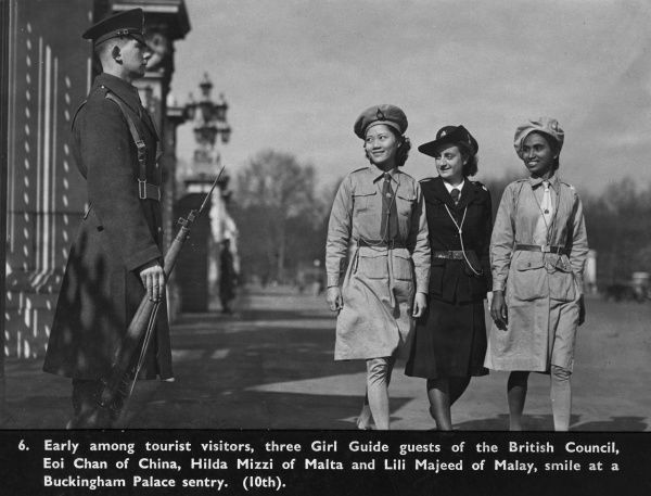 Early among tourist visitors, three Girl Guide guests of the British Council, Eoi Chan of China, Hilda Mizzi of Malta and Lili Majeed of Malay (Malaysia), smile as they walk past a Buckingham Palace sentry