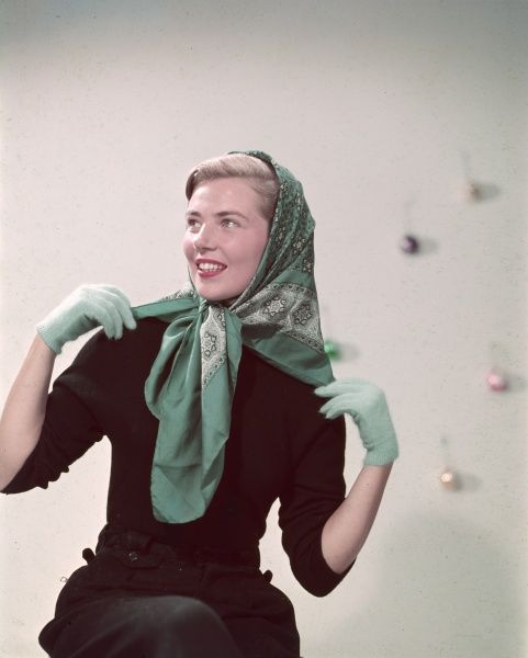 A girl poses wearing a head scarf (quite fashionable in the 1950s and not just worn by the Queen)