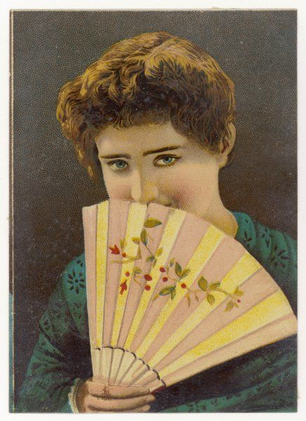 A shy young woman hides her mouth and lower face behind a fan which is ornamented with a design incorporating foliage, berries & flowers. Date: 1880s