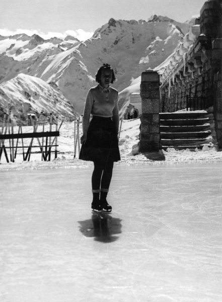 A teenage girl ice skating in an Alpine setting. Date: 1930s