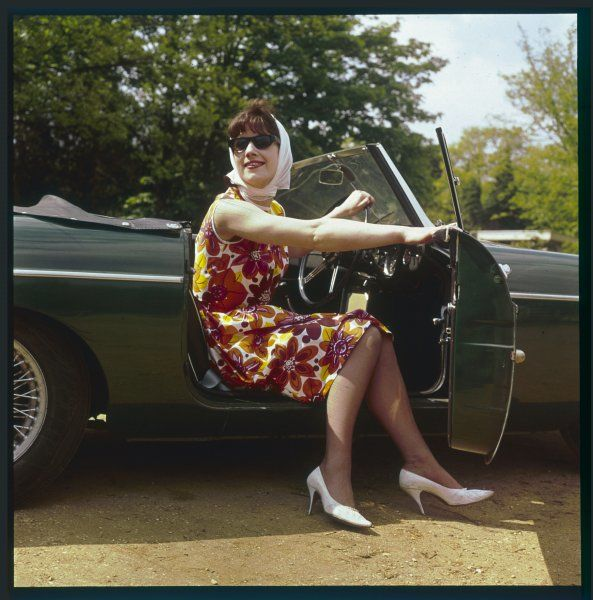 A girl in a classic racing green 'MGB' sports car. Introduced in autumn 1962, the MGB was originally available only as a convertible and proved to be an immediate hit