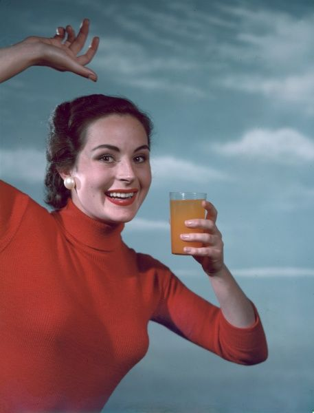 A gleeful brunette model in red polo neck jumper & pearlised earrings gives a cheery wave as she holds up a glass of orangeade or orange squash