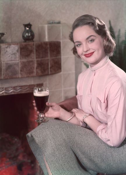 A smiling, respectable looking blonde, wearing a blouse, tweed skirt & pearls, enjoys a glass of stout while sitting in front of a modern tiled fireplace