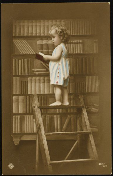 A young girl has climbed to the top of the library steps to remove a fascinating looking book from the shelf