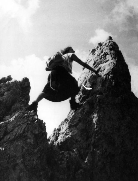 This woman rock climber doesn't look very safe as she straddles two rocks! Date: 1930s