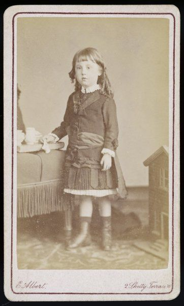 A little girl wears a costume of long jacket bodice with ruched trim at the hem, broderie Anglaise collar & cuffs, short kilted skirt, sash, socks & boots