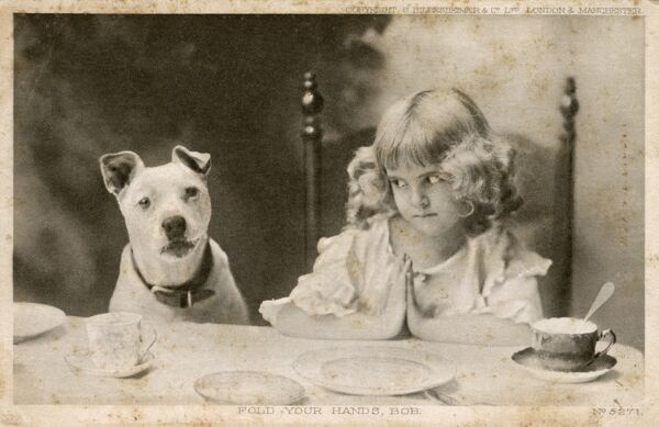 """Fold Your hands Bob!"" A pretty young girl says Grace, but is slightly affronted that her pet dog Bob is unwilling to join in and fold his paws together respectfully.... Date: circa 1910"
