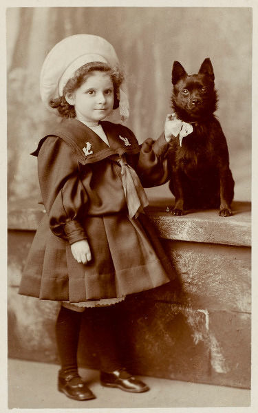 A small girl in a sailor suit poses with her schipperke