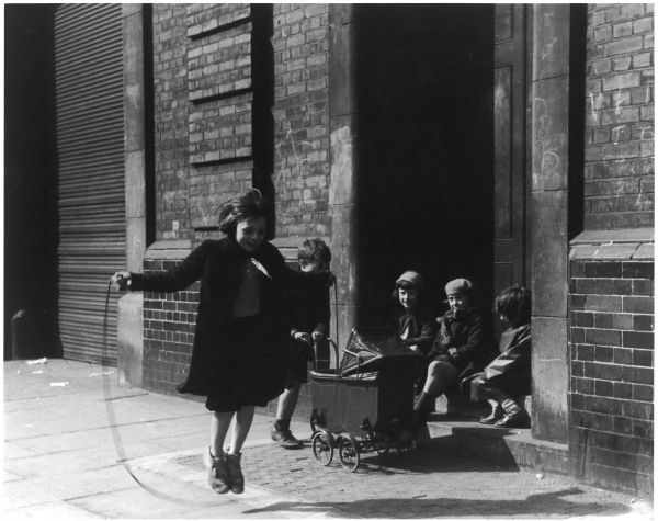 A girl skips along the pavement, watched by three friends