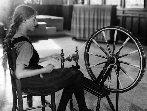 Teenage girl with her hair in a plait, using a spinning wheel. Date: 1930s