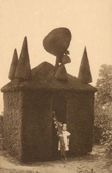 A young Girl holding a tall sheaf of flowers and sticks, stood alongside a magnificent intricate topiary 'Wendy' house at Huckelhoven, a town in the district Heinsberg, in North Rhine-Westphalia, Germany. Date: circa 1910s