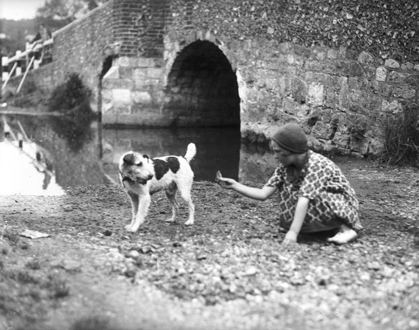A girl squatting down beside a river, calling a wire-haired fox terrier towards her