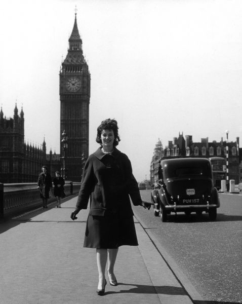 A carefree young 'Girl About Town' walking across Westminster Bridge, Big Ben behind her, in 'Swinging London'! Date: 1960s