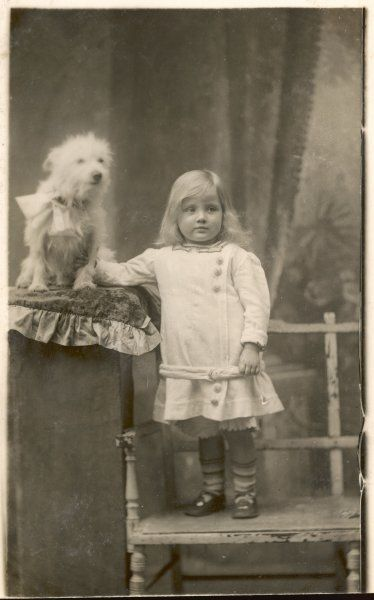 A small girl poses with a small white dog