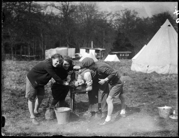 Four girls preparing a meal around the camp fire at Boxhill, Surrey, England