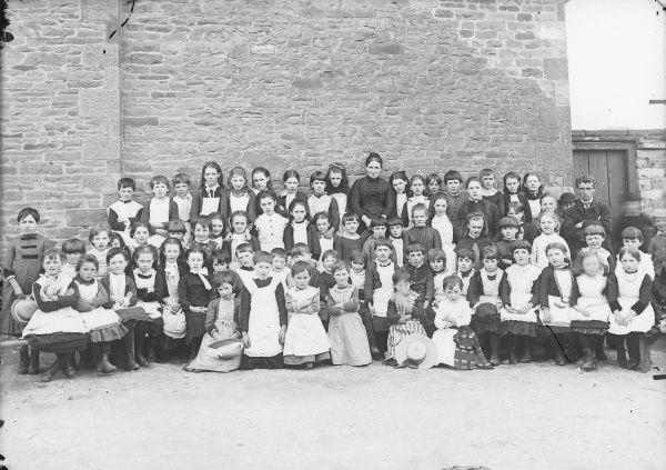 A group photo of the girls' class at Crickhowell School, Crickhowell, Powys, Mid Wales. There are two teachers, one male, one female