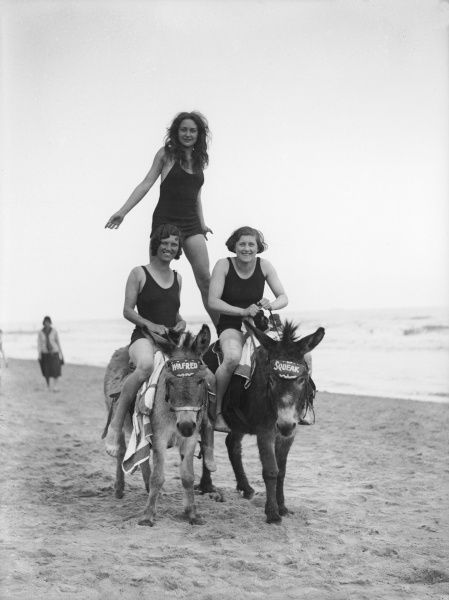 Three 'thoroughly modern' girls in their swimming costumes, taking a ride on 'Wilfred' and 'Squeak', two donkeys, on the beach at Ramsgate, Kent, England