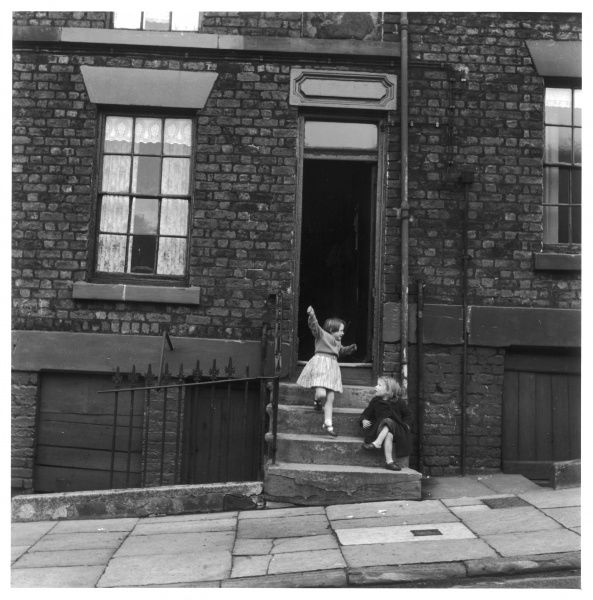 Two girls chatting and playing on a doorstep