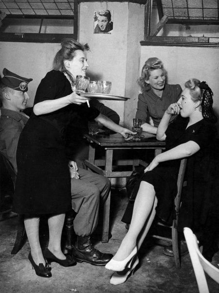 Two glamorous girls entertain an American GI, whose cap badge indicates he is an Infantry Paratrooper in an unidentified bar in London during World War II, while a third waits table. There is a picture of James Stewart on the wall