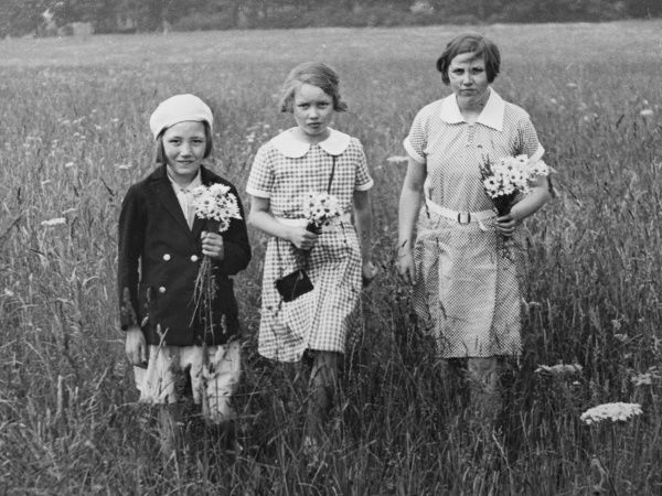 Three young girls stand in a field at Box Hill, Surrey, England. Each holds a poesy of daisies