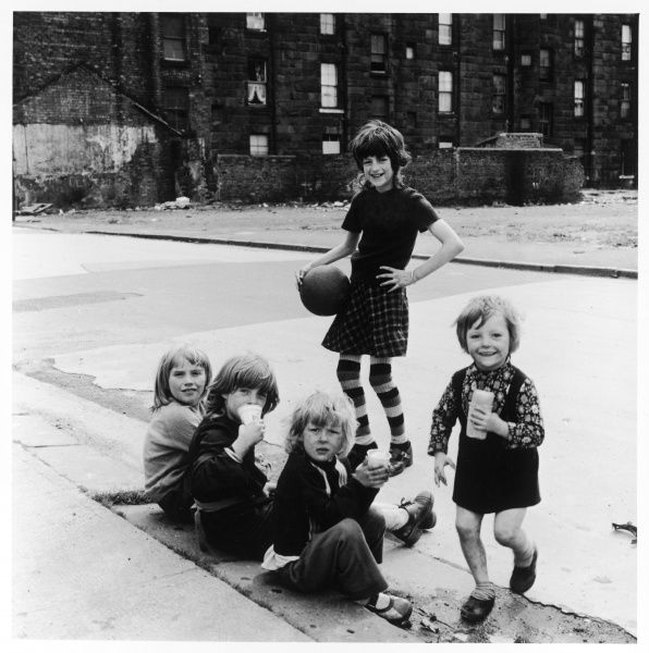 A group of girls sitting on a kerbstone in an East Glasgow street, Scotland. One of the girls, wearing stripy socks, is holding a football