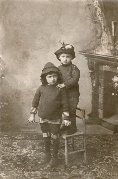 Two girls pose for their photograph, one of them standing behind the other on a chair. They are both wearing little hats, and one holds a stick like a riding crop. They are from the settlement of Kostel (also known as Podivin) in South Moravia