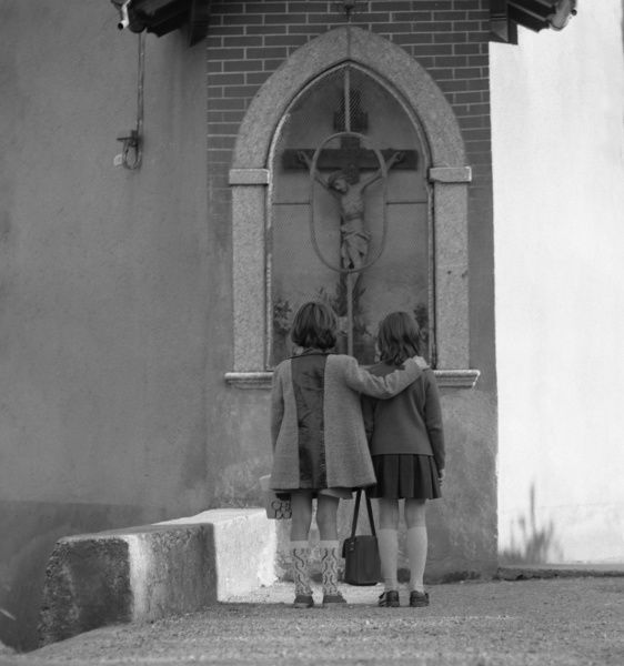 Two girls looking at a crucifix set in a gothic arch-shaped niche outside a church