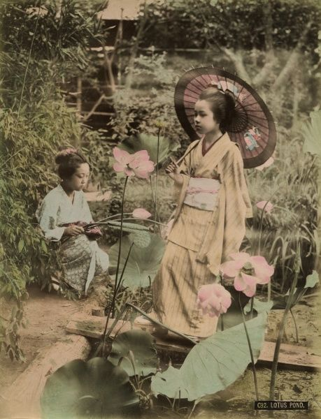 Two young Japanese girls, one holding a parasol, with lotus flowers