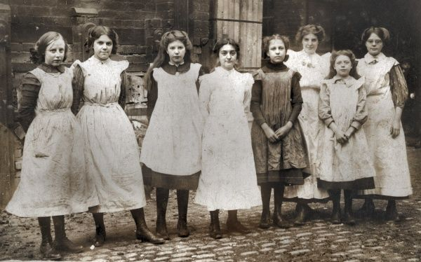 A group of working-class girls stand outside a workshop, possibly connected to the clothing trade