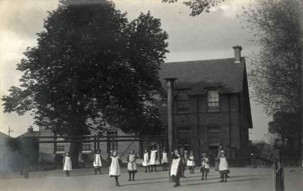 The girls' playground at a what may be children's home, workhouse, or similar institution. The girls are wearing a typical dress of such an establishment and some are dancing around a maypole. Date: Date unknown
