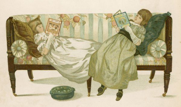 Two girls sprawled at opposite ends of a sofa engrossed in their books