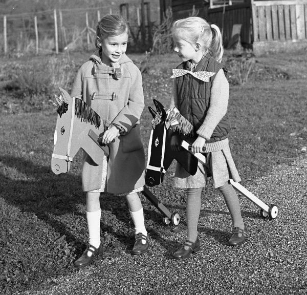 Two girls (non-identical twins) riding their hobby horses