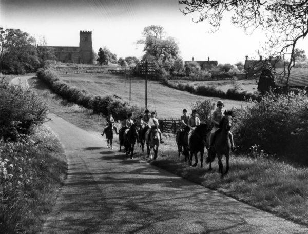 Girls riding horses on a country lane near Great Brington, Northamptonshire, England. Date: 1960s