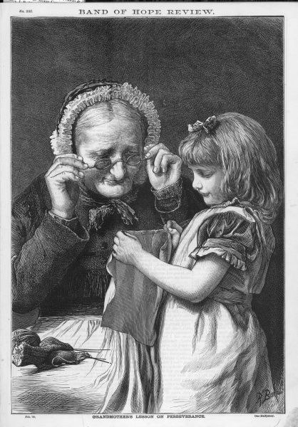A young girl shows her sewing to her grandmother who inspects it over the top of her spectacles. Date: 1880