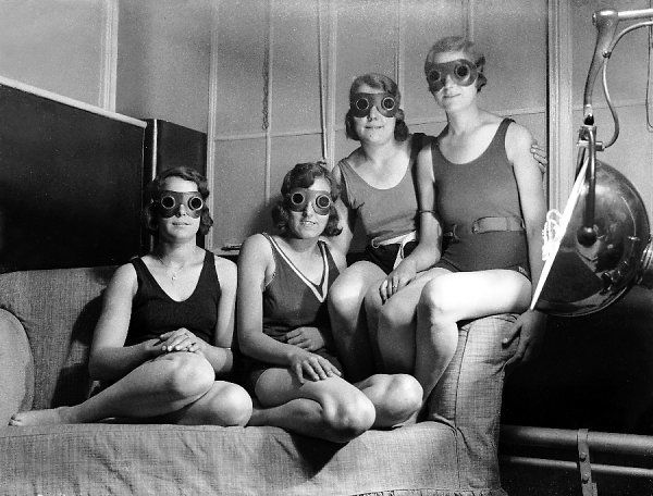 A group of factory girls from Leeds, Yorkshire, England, topping up their tans with the aid of sunray treatment. Shame about the goggles