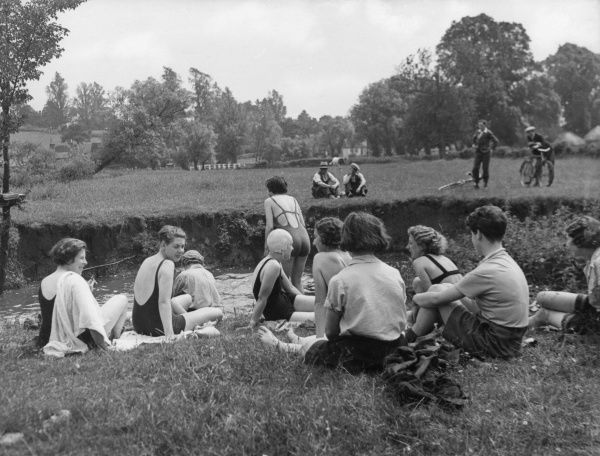 Young ladies of the 'R.C.C.' club take a cold dip in a stream after a picnic lunch, watched by a group of local men across the riverbank! Date: 1930s