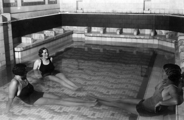 Three young women with 'Marcel Wave' hairstyles, relaxing together in an indoor Turkish bath. Date: 1930s