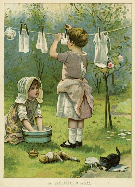 Two girls peg out their dolls' laundry on a washing line in the garden
