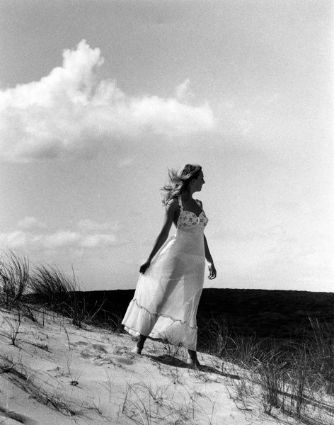 A glamour girl poses in her see-through negligee on the sand dunes on a beach in Cornwall
