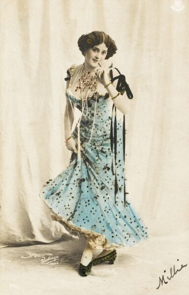 A hand-coloured photographic postcard of a shy young lady in a bright low-cut blue dress with a finger to her mouth and wearing a long string of pearls