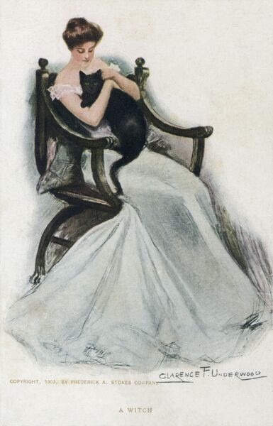 'A Witch'. A glamourous model holding a black cat! Both sit serenely in a fine wooden chair