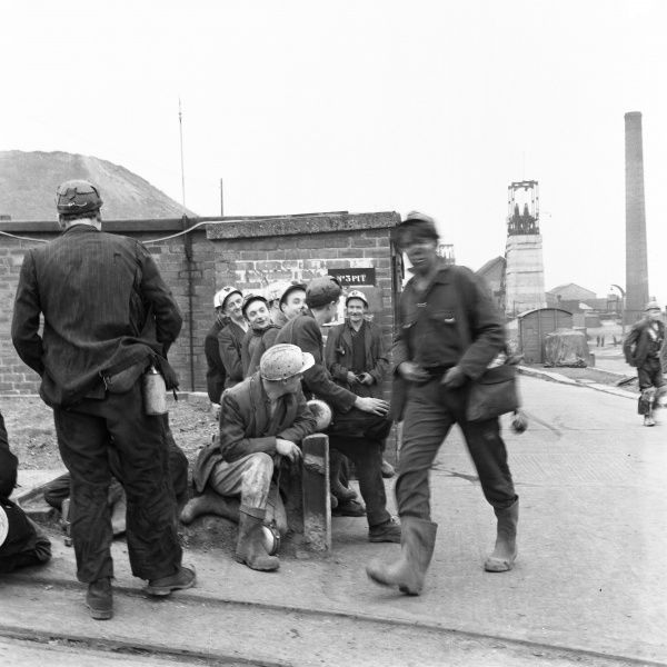 A miner from Glapwell Colliery, north east Derbyshire, black and dirty from the pit at the end of his work shift. A group of cleaner looking miners wait, possibly to start their shift. Glapwell colliery closed in the 1970s