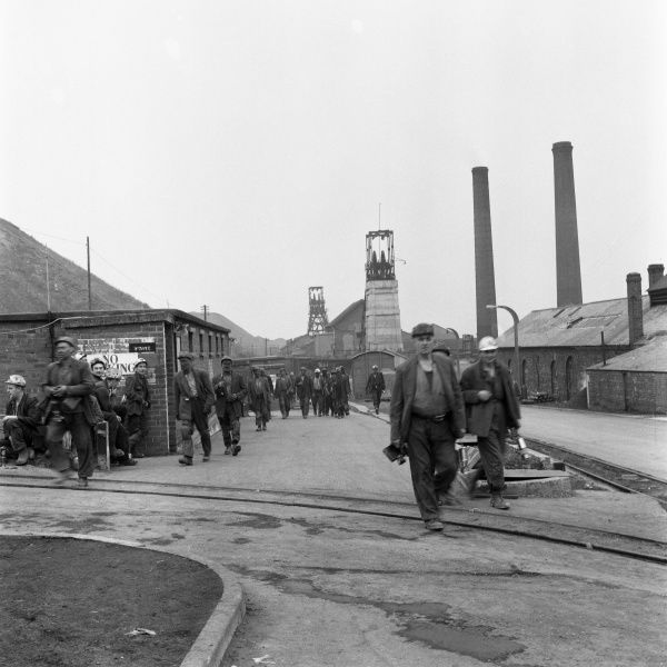 Miners from Glapwell Colliery, north east Derbyshire, black and dirty from the pit at the end of their work shift. Some carry miners lamps. A group of cleaner looking miners wait, possibly to start their shift. Glapwell colliery closed in the 1970s