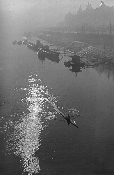 Homeward bound : A canoer rows up the glistening River Danube at sunset, Budapest. Hungary. Date: 1930s