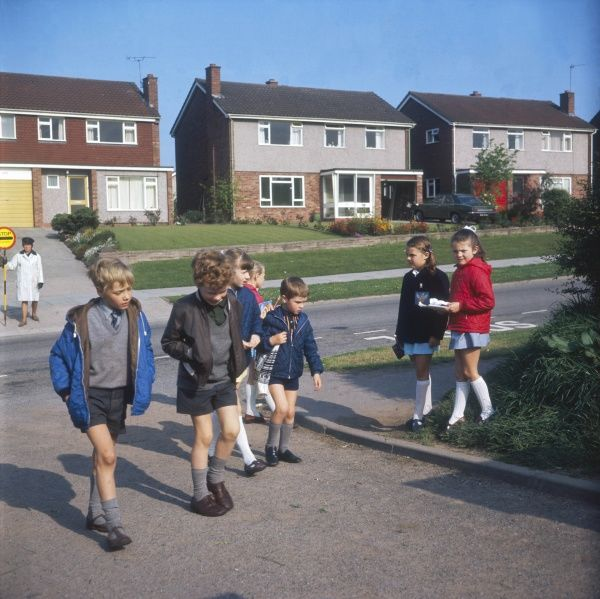 Boys and girls leave a housing estate and set off for school. The lollipop lady, who has presumably just assisted them to cross the road, is in the background